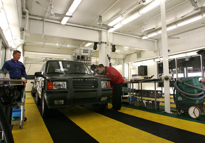 Technicians at Fine Airport Parking in Tulsa inspect a paint defect on a vehicle before removing it during a detailing.