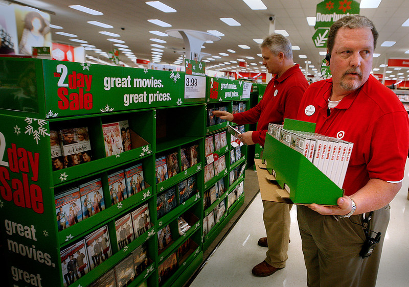 On Black Friday in Tulsa Target Store Manger Bill Dockum helps redistribute a display of movie DVD's shoppers had nearly emptied during the first day of Christmas shopping.