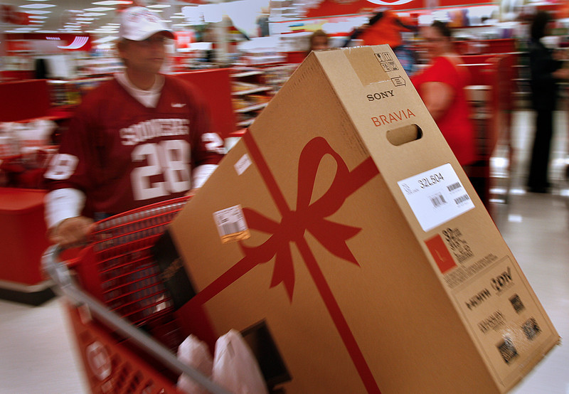 On Black Friday a shopper wheels a new TV out of the Target checkout line.