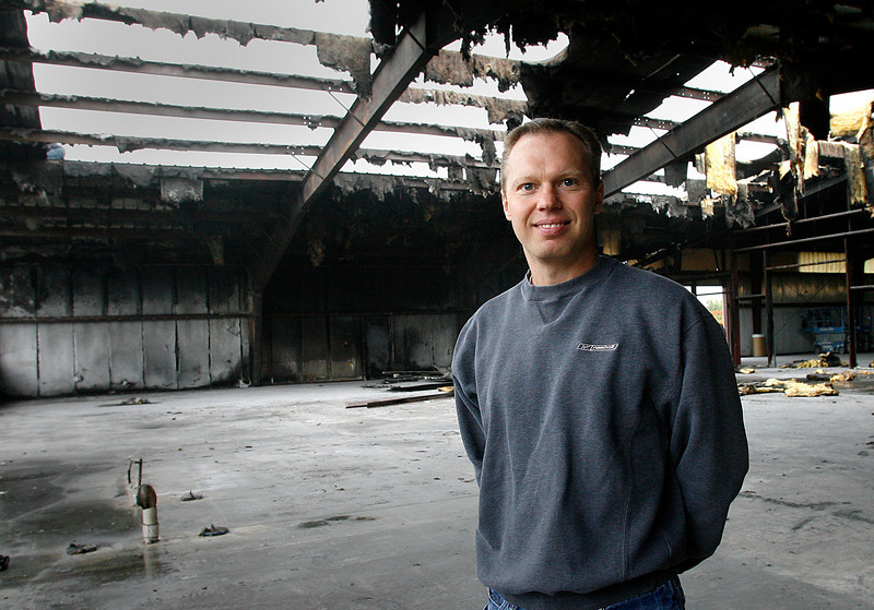 OK Filter Co-Owner Bret Methvin stands amid the remains of his manufacturing facility after a fire destroyed it.