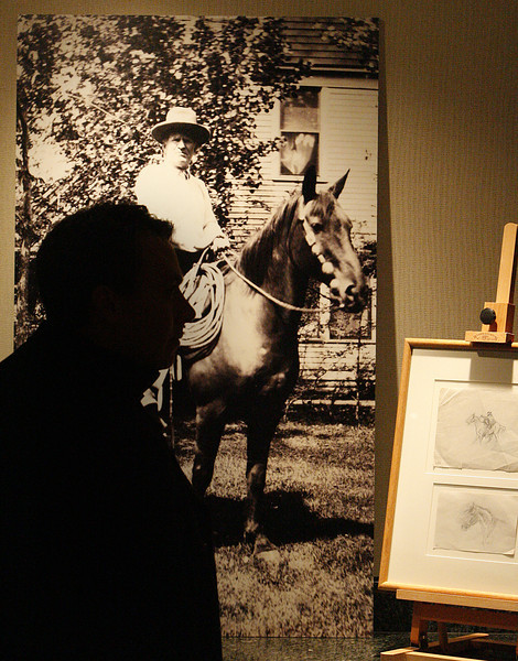 At the Gilcrease museum announced Thursday of the purchase of a large collection of the artist Charles M Russellís works and memorabilia a spectator is silhouetted against a photo of the artist.