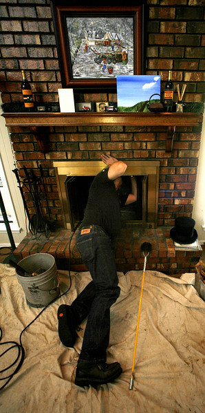 David Harris of Black Hat Cleaning Services inspects and cleans a fireplace in South Tulsa. Harris has been a chimney sweep for about 30 years.