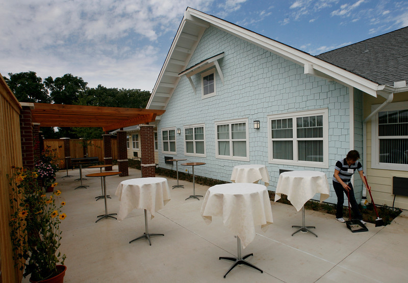 Staff at the Alzheimerís Memory Support Residence sweep up the patio to prepar for the Grand Opening of their South Tulsa facility Thursday.