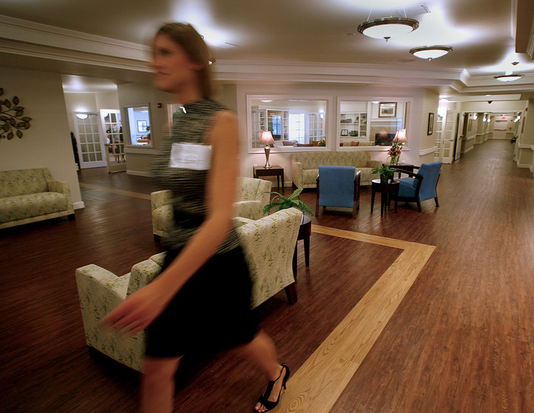 Valarie Montgomery, Life Enrichment Director at the Cypress Springs Alzheimers Memory Support Residence walks through the main lobby while preparing  for the Grand Opening of their South Tulsa facility Thursday