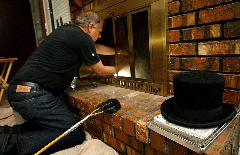 David Harris of Black Hat Cleaning Services cleans a fireplace in South Tulsa. Harris has been a chimney sweep for about 30 years.