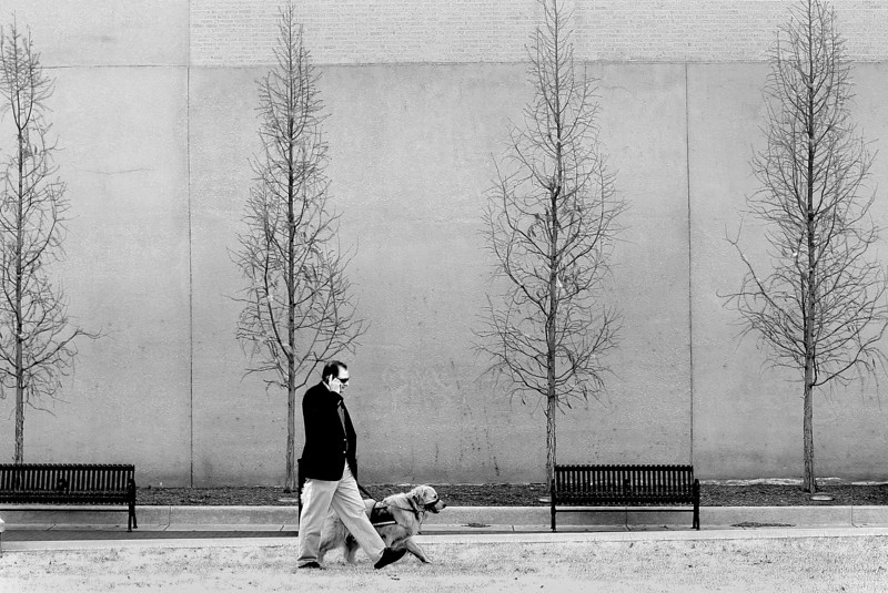 A man walks and talks during the lunch hour in the H.A. Chapman Centennial Green park in downtown Tulsa.
