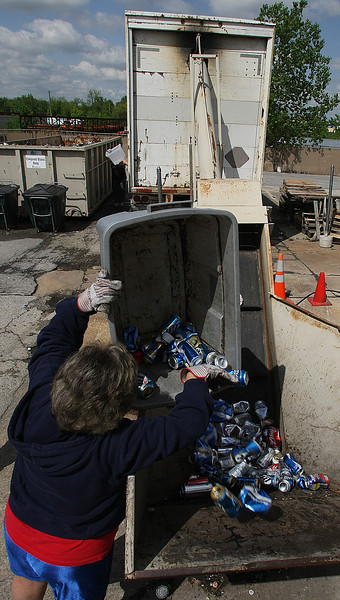 Robin Layton dumps aluminum cans in the crusher at the Broken Arrow MET Recycling center.