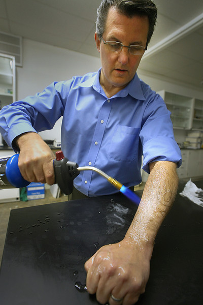 Mitch Freeman, VP of Product development for Global Safety Labs, uses a blow torch to demonstrate the fire resistance of the companies products which has been applied to Freemans arm.