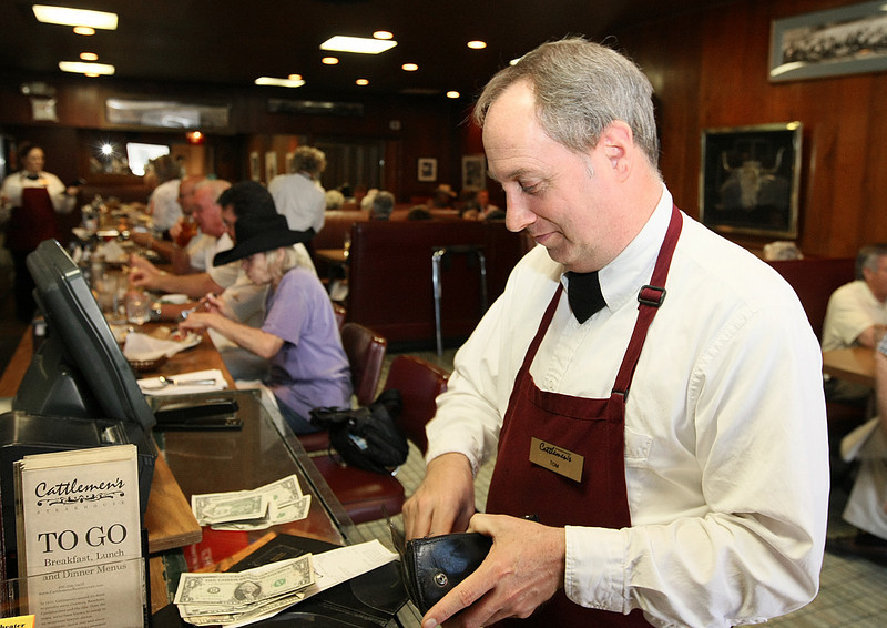 Tom Freeman, waiter at Cattlemen's Cafe, counts a payment at the cafe Friday. PHOTO BY MAIKE SABOLICH