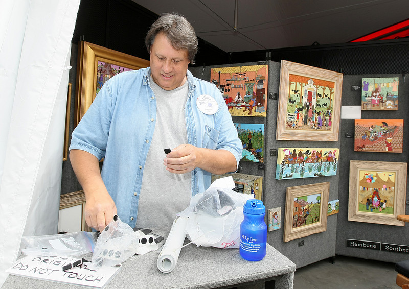 Hambone with Hambone Southern Creole Folk Art sets up his art display for today's 2010 Festival of the Arts. PHOTO BY MAIKE SABOLICH