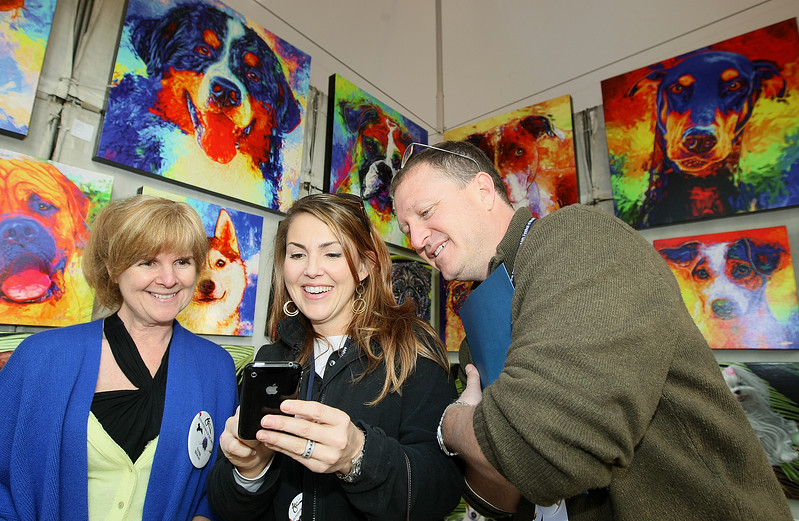 Heidi and Chuck Cohn, middle and right, show artist Jane Billman a picture of their dog at the 2010 Festival of the Arts Tuesday morning. The couple is commissioning the artists for a painting of  their daughter's dog. PHOTO BY MAIKE SABOLICH
