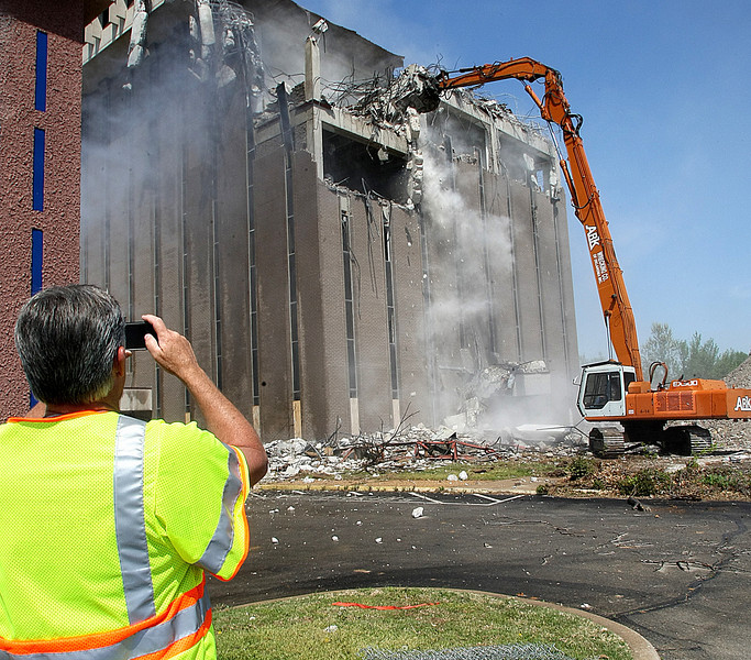 A member of the Oklahoma Transportation Authority punches off a photo as another building falls to the wrecking ball to make way for the Interstate 44 widening project in Tulsa.