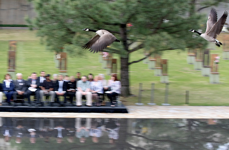 Wild geese fly over the reflectiong pool during the 15th Anniversary Rememberance Ceremony at the Oklahoma City National Memorial Monday. PHOTO BY MAIKE SABOLICH