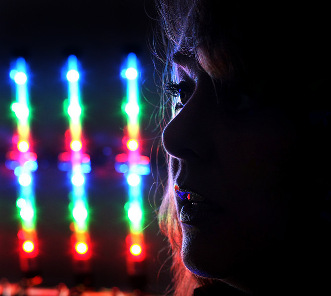 Dana Stefanoff, President of Crossroads LED's in Collinsville.Is silhouetted against LED lights the company produces.