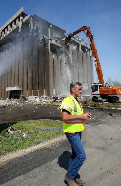 A member of the Oklahoma Transportation Authority walks away after taking a few photos of the building demolition making  way for the Interstate 44 widening project in Tulsa.