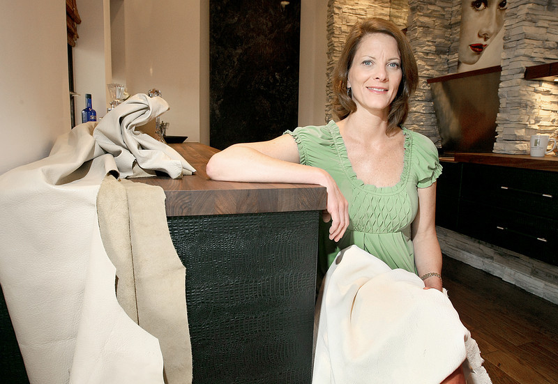 Karen Black, owner of A Karen Black Company, an interior design and manufacturing business in Oklahoma City, with leather samples and eather-covered bar kitchen furniture. Black now has three patents pending for the use of leather or other materials to cover cabinet doors. PHOTO BY MAIKE SABOLICH