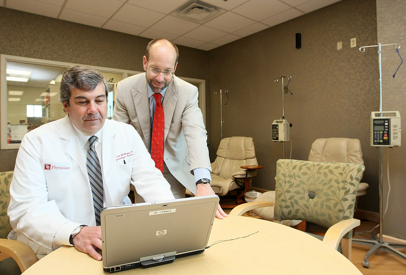 University of Oklahoma's Dr. Scott McMeekin, chief of gynecologic oncology, and Dr. Robert Mannel, director of the OU Cancer Institute, look at patient information in the patient care facility Tuesday. PHOTO BY MAIKE SABOLICH