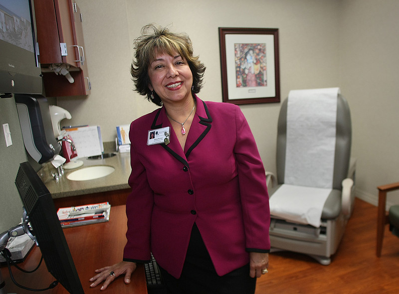 Pausing for a photo in an exam room of the newest addition to the Cancer Treatment Centers of America is Elena Roman, Chief Operating Officer in Tulsa.
