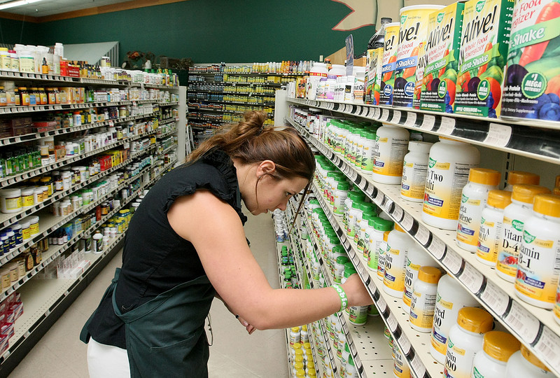 Dacia Hall organizes one of the supplements' isles at Akins Natural Foods Thursday. PHOTO BY MAIKE SABOLICH