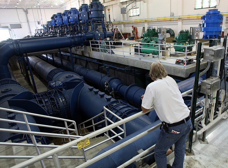A worker observes maintenance work being done in the pump room of the Mowhawk Water Treatment plant in Tulsa.