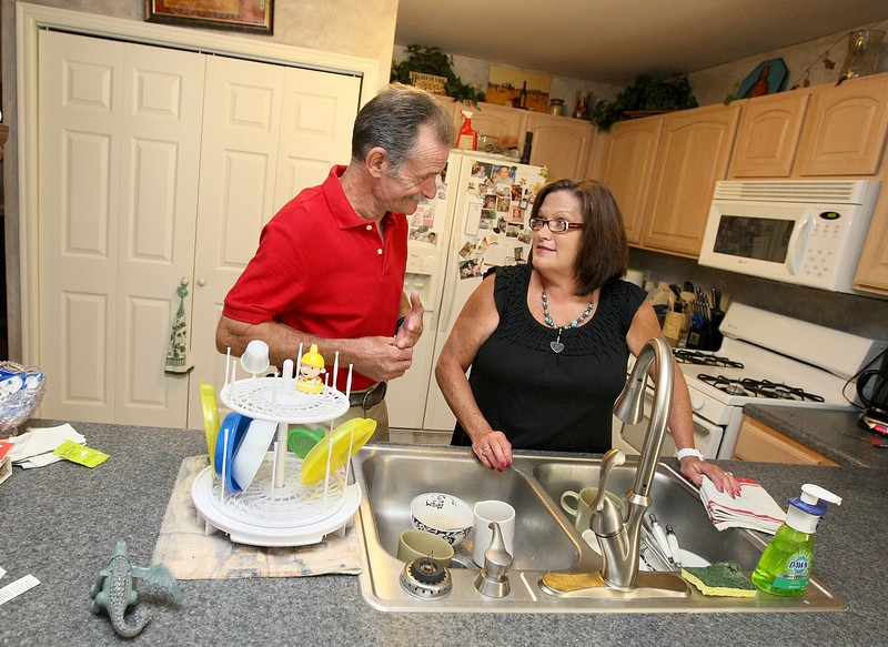 Al  and Vicki Lea do the dishes together at their house on which they just recently closed on a Federal Housing Administration mortgage to become owners of their home. The home purchase by the couple was the first transition from the rent-to-own program to home ownership with a mortgage for City Care's program. PHOTO BY MAIKE SABOLICH