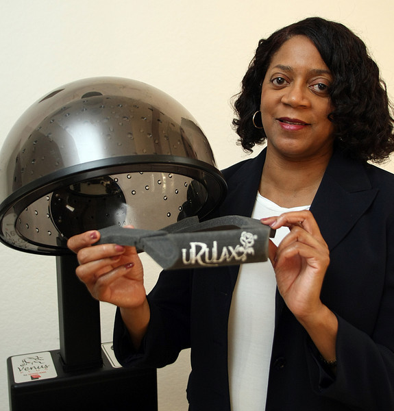 Rose Hardwickhold a device she invented, the URULAX, a shield that protects your face when you sit under hair salon dryers.