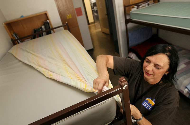 Gloria Howell, clientat the City Rescue Mission, puts new bed sheets on a bunk bed in one of the shelter rooms Monday. PHOTO BY MAIKE SABOLICH