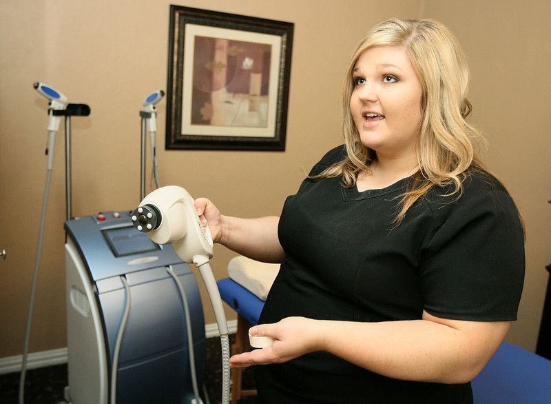 Brittaney Waugh, aesthetician with Body Trends, explains  the Accent XL, one of the machines used in the spa's treatment plan, Monday. PHOTO BY MAIKE SABOLICH