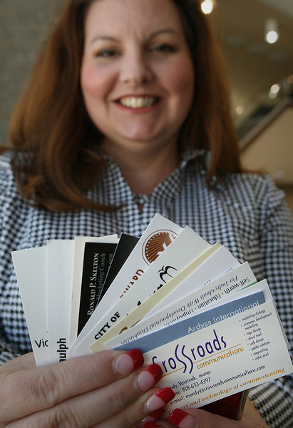 Mandy Vavrinak, Owner of Crossroads Communications, holds a few of the many business cards she keeps.