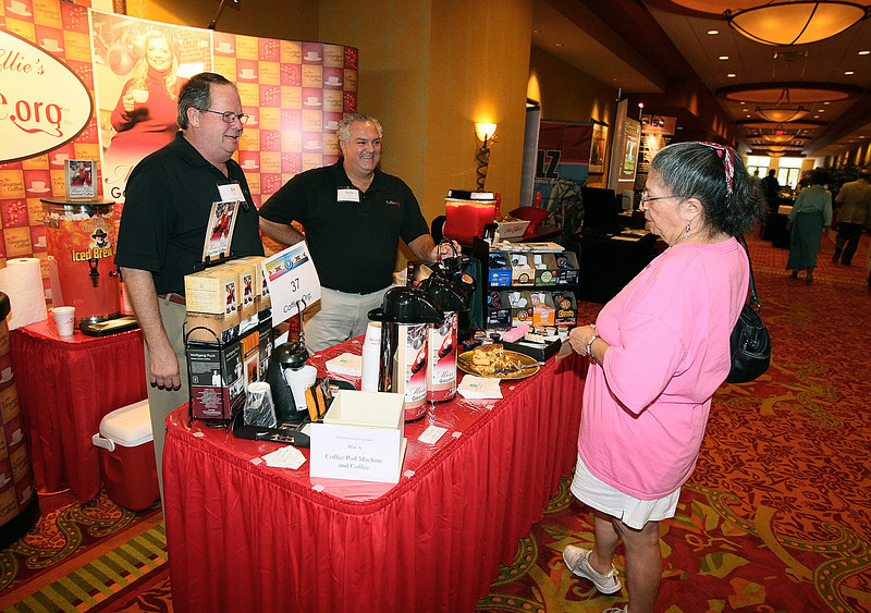Norma Westphal gets coffee from William McClure and Drew Bryars with Coffee.org at the Indian Country Business Summit at the Embassy Suites in Norman Tuesday. PHOTO BY MAIKE SABOLICH