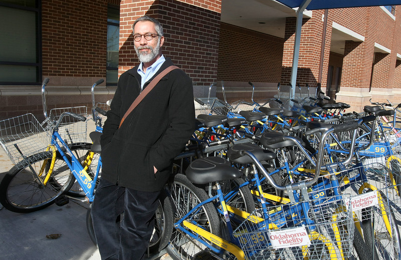 Tim Tillman, alternative transportation coordinator at the University of Central Oklahoma, with some of the University's public bikes in front of the Wellness Center Thursday. PHOTO BY MAIKE SABOLICH