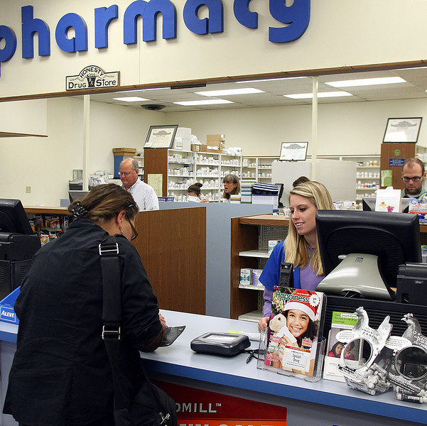 Spoon Pharmacy clerk Angie Nix helps a customer pick up her prescriptions at the Sand Springs drug store.