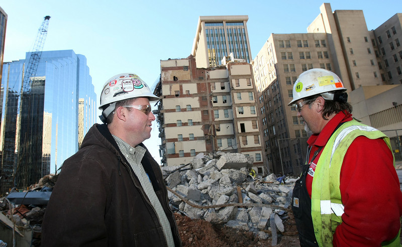 Project Manager Chris Kates talks to Ross Kasner, equipment operator at the Sandridge construction site downtown Tuesday. PHOTO BY MAIKE SABOLICH