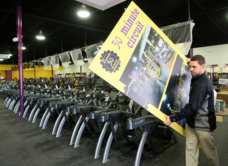 Kyle Tosh, general manager at Planet Fitness, carries an advertising board through the new gym on Northwest Expressway Wednesday. PHOTO BY MAIKE SABOLICH
