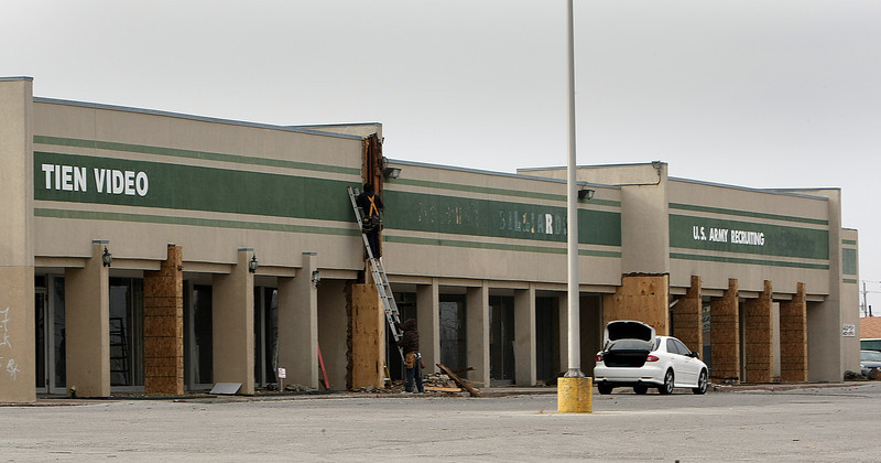 Workmen do some repair work on a shopping center at 11632 E 21st Street in Tulsa that recently sold for $1.3 Million.