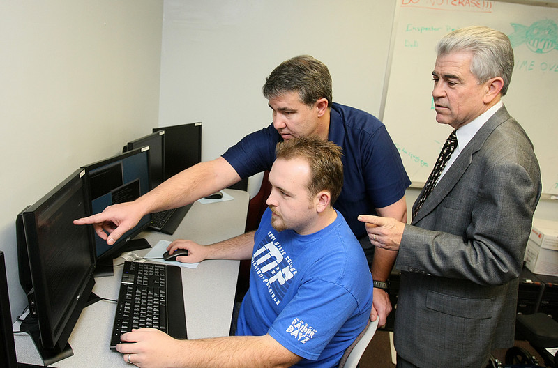 Rose State College's cyvbersecurity Professor Ken Dewey, cybersecurity student student Caleb Glave and Dr. Dave Wagie check outr the web site securitywizardry.com at the college.  PHOTO BY MAIKE SABOLICH