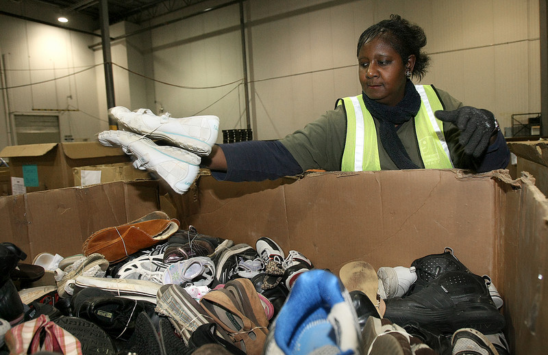 Aretha Brown, processor at Goodwill Industries, sorts through shoes for recycling Wednesday at the Blackwelder location. PHOTO BY MAIKE SABOLICH