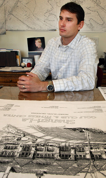 Jason Sheffield, General Manager of the Shangri-La Country Club in Afton, in his office with the blueprints of the club house on the desk in front of him.