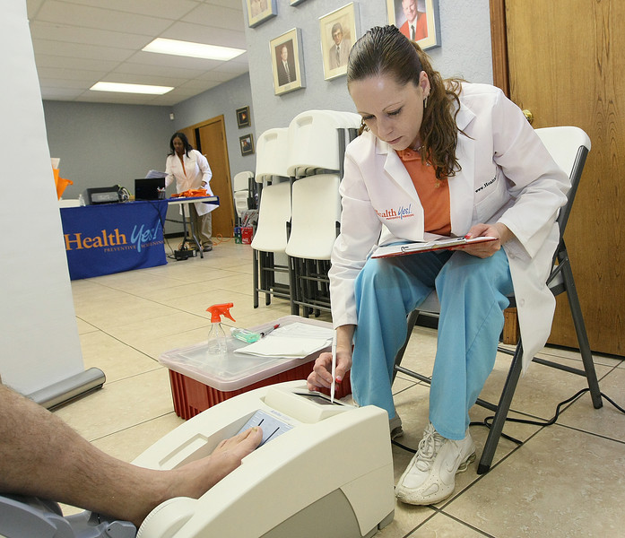 Traci Caldarone, medical assistant with Health Yes, performs a bone density test with ultrasound during a medical screening event at the Oklahoma City Fire Department Local 157 Union Hall Thursday. PHOTO BY MAIKE SABOLICH