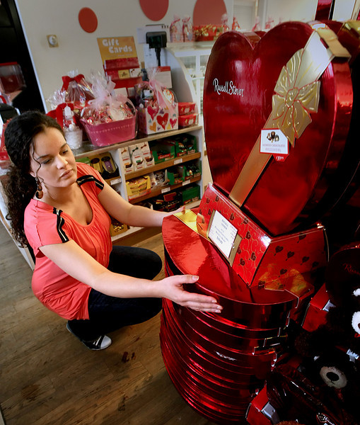 Lindsey Curtis straightens a stack of heart shaped Russell Stover candy boxes ready for Valentines Day sale.