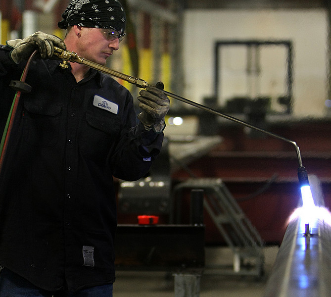 At Pelco Structural in Claremore a workman heats a section of a pole destined to be used as a street light support.