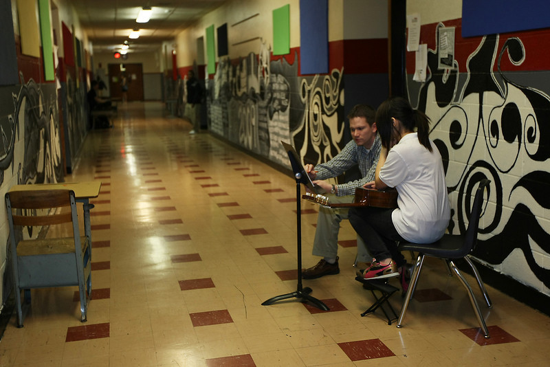 An instructor and student sit in the hallway of Harding Fine Arts Academy Wednesday afternoon. The Fine Arts Academy shares a building with Harding Charter Prepatory High School and the two charter schools are involved in a dispute over the building's lease.
