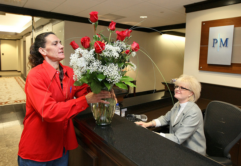 Nancy Maxwell delivers OKC Florist roses at Phillips Murrah in the Corporate Towers downtown Thursday. Receptionist Marilyn Carter admires the roses. PHOTO BY MAIKE SABOLICH
