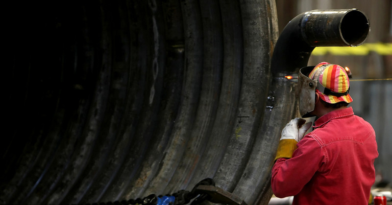 Welder James Nelson works on a section of a large heating coil being produced at the American Pipe Bending company in Tulsa.