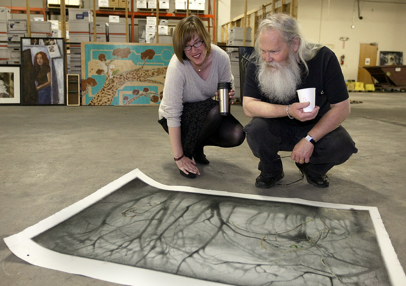 Dr. Margo Shultes von Schlageter and John Seward pick out art work for the Momentum art show at the Goodwill Warehouse.  PHOTO BY MAIKE SABOLICH