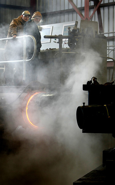 Employees of the American Pipe Bending company in Tulsa use electrical induction to heat and bend a section of 36 inch pipe.