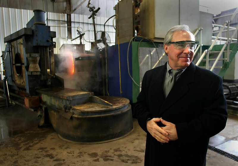 Larry Houston, President of American Pipe Bending Company, stands in front a machine the uses electrical induction to heat and bend large diameter pipe.