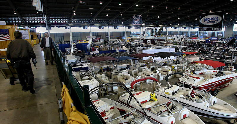Vendors roll in the finishing touches in preparation for the Tulsa Boat, Sport & Travel Show Monday night.