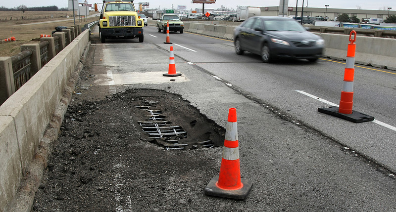 Traffic detours around a half lane wide pothole on an I-44 Bridge on the East side of Tulsa.  The first pothole occurred on the same bridge just two day prior and damaged over a dozen vehicles before traffic could be routed around the hazard.