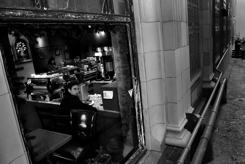 While eating lunch a customer watches pedestrians out the window of Topecca Coffe in downtown Tulsa.